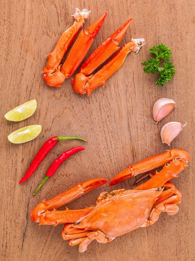 Den kokta krabban klöser med limefrukt, chili, vitlök och persilja på trä royaltyfri foto