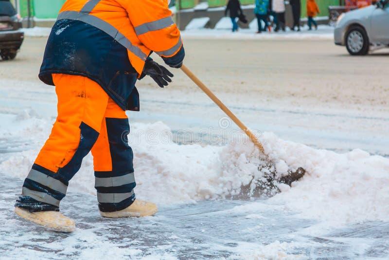 Den kollektiva servicearbetaren sopar snö från vägen i vinter, rengörande stadsgator och vägar efter snöstorm moscow russia fotografering för bildbyråer
