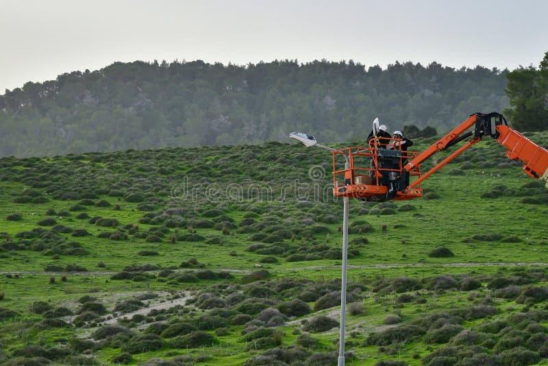 Den kommunala arbetarmannen med hjälmen och säkerhetsskyddsutrustning installerar nya diodljus fotografering för bildbyråer
