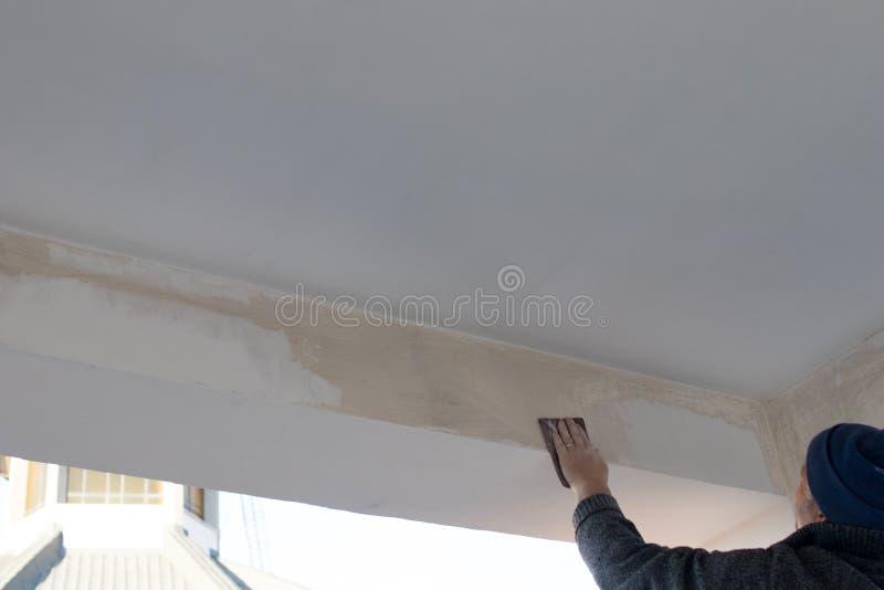 Den kompetenta arbetaren fördelar stuckaturen och målarfärg på en stråle av en terrass D royaltyfri fotografi