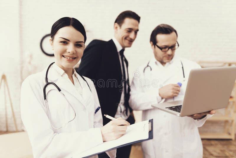 Den kompetenta doktorn visar på bärbar datorresultat av läkarundersökning av den lyckade affärsmannen i regeringsställning arkivfoton