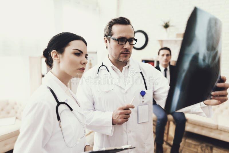 Den kompetenta kirurgen och sjuksköterskan studerar nära röntgenstrålen av bäcken- ben av patienten Mottagande på kirurgen fotografering för bildbyråer