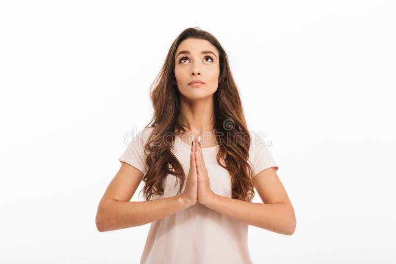 Den koncentrerade brunettkvinnan i t-skjorta som ber med, ber gest royaltyfri foto