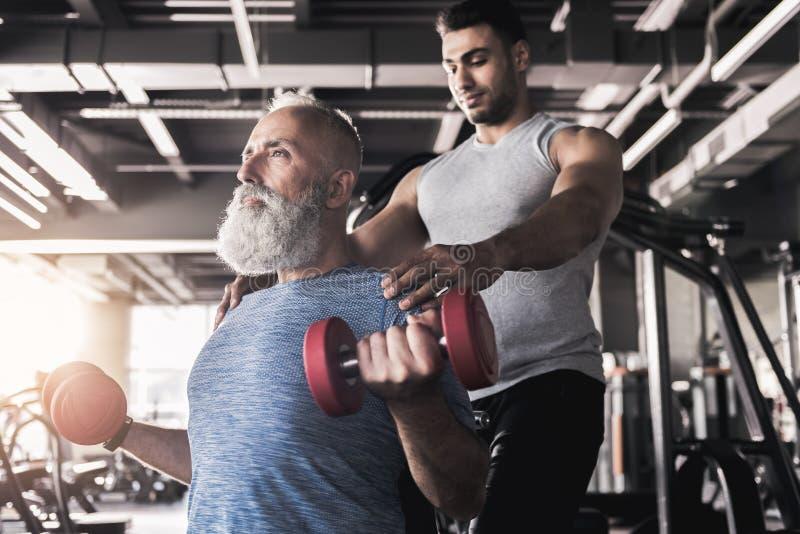 Den koncentrerade höga mannen utbildar hans biceps i idrottshall royaltyfria bilder
