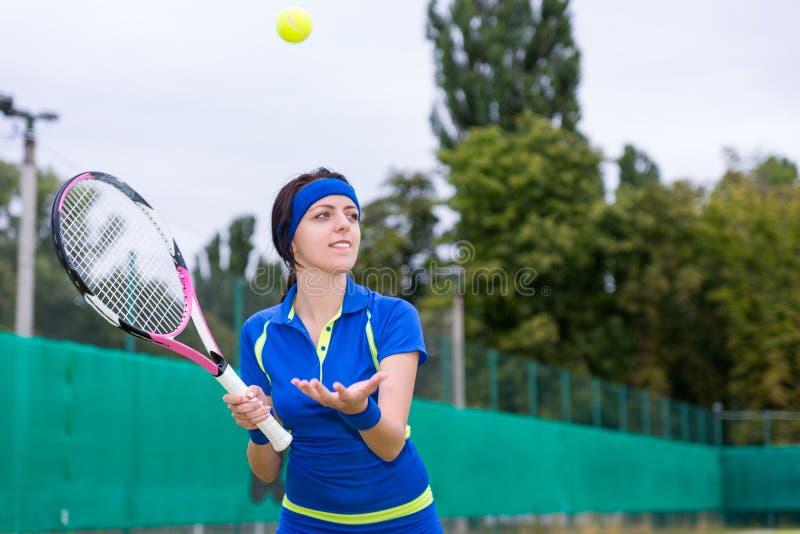 Den koncentrerade kvinnliga tennisspelaren kastar bollen under en match arkivfoton
