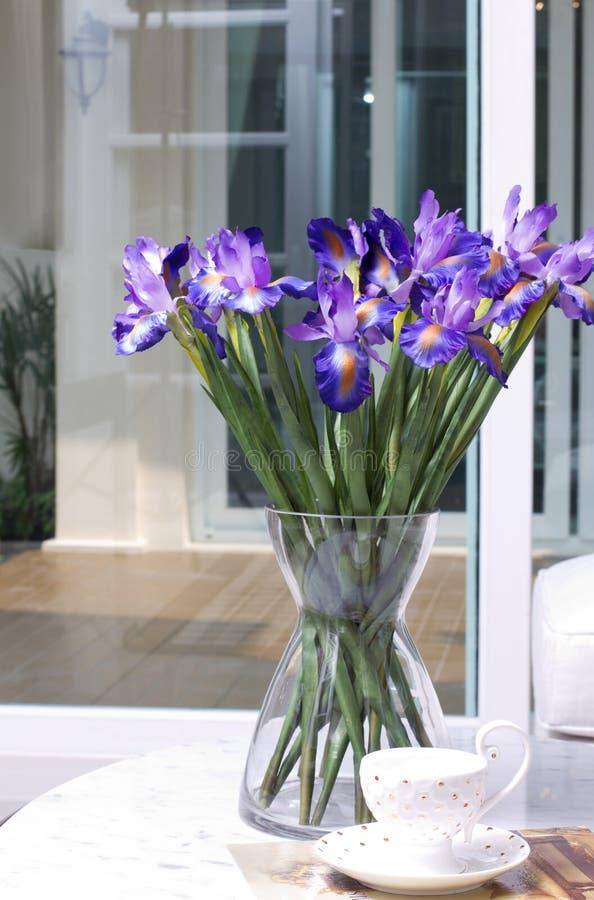 Den konstgjorda irisen blommar i en glass vase royaltyfri bild