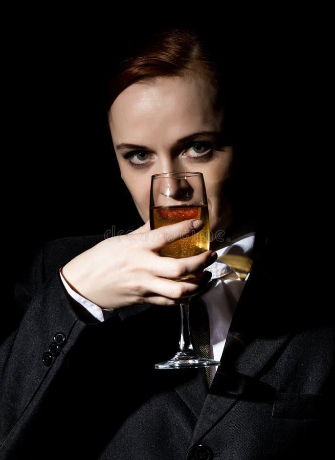 Den konstiga kvinnan i en dräkt för man` s dricker champagne på en mörk bakgrund royaltyfri fotografi