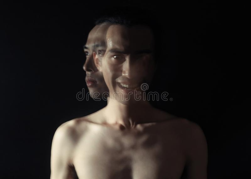 Den konstiga mannen stod i mörkret med ett ont leende på hans framsida som ser kameran royaltyfri bild