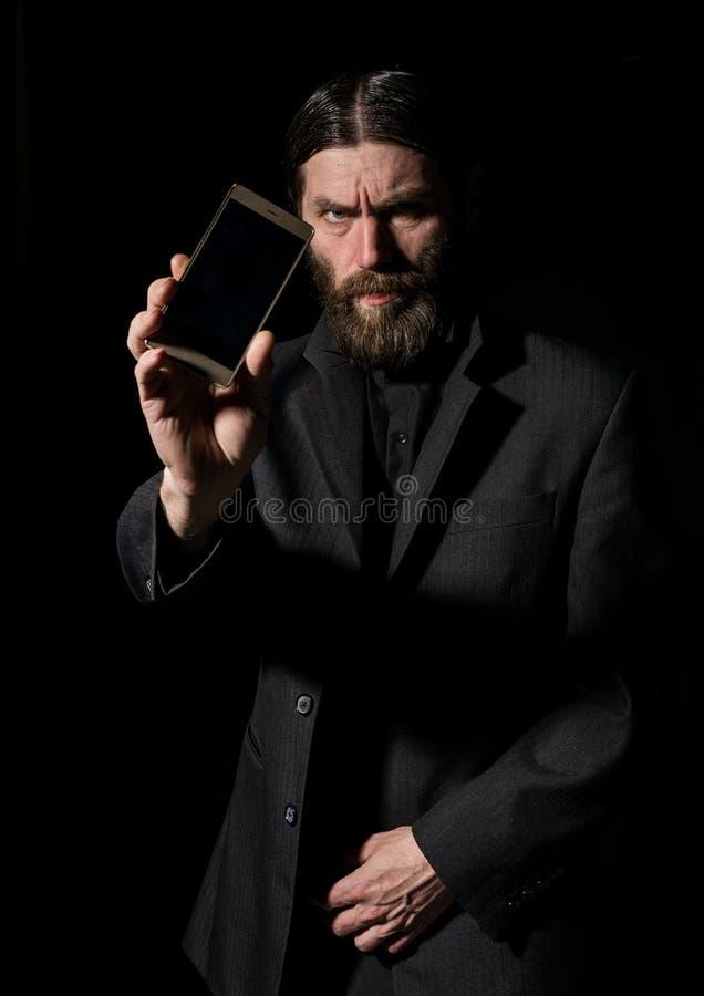 Den konstiga skäggiga höga prästen med en smartphone, den skäggiga gamala mannen kallar på en mörk bakgrund arkivbilder