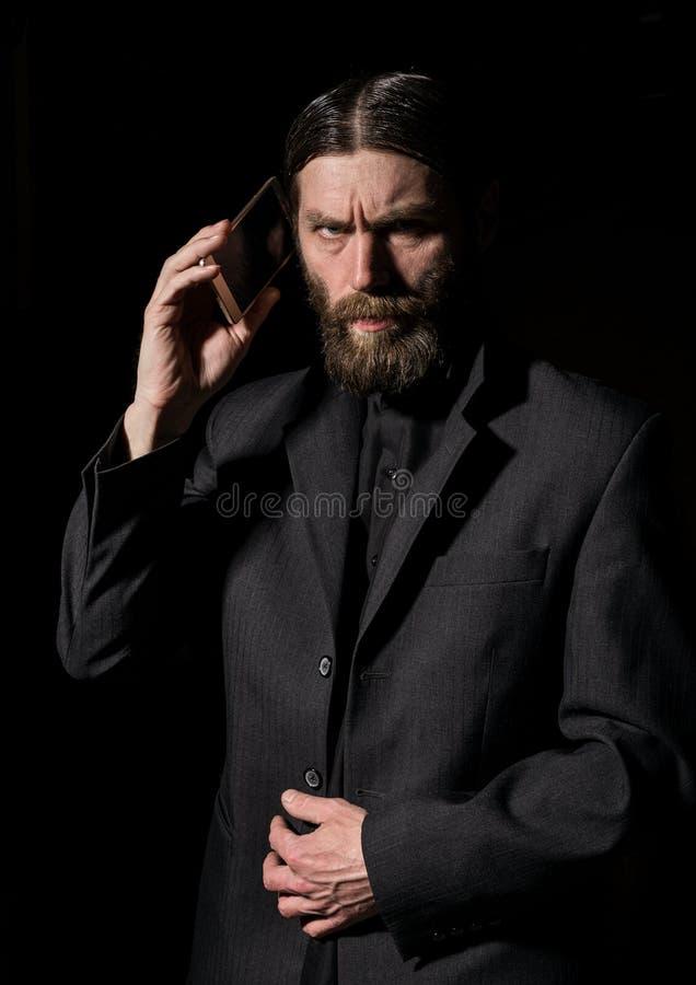 Den konstiga skäggiga höga prästen med en smartphone, den skäggiga gamala mannen kallar på en mörk bakgrund royaltyfri foto