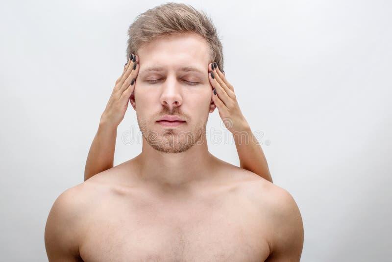 Den kopplade av ställningen för den unga mannen med ögon stängde sig Kvinna'händer är på huvudet Grabben är shirtless bakgrund is fotografering för bildbyråer