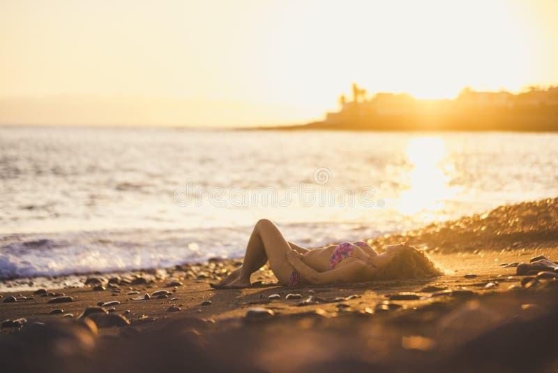 Den kopplade av unga caucasian damen lägger ner på kusten nära havvågorna på stranden sommarsolnedgångtid för semester och lopp arkivfoton