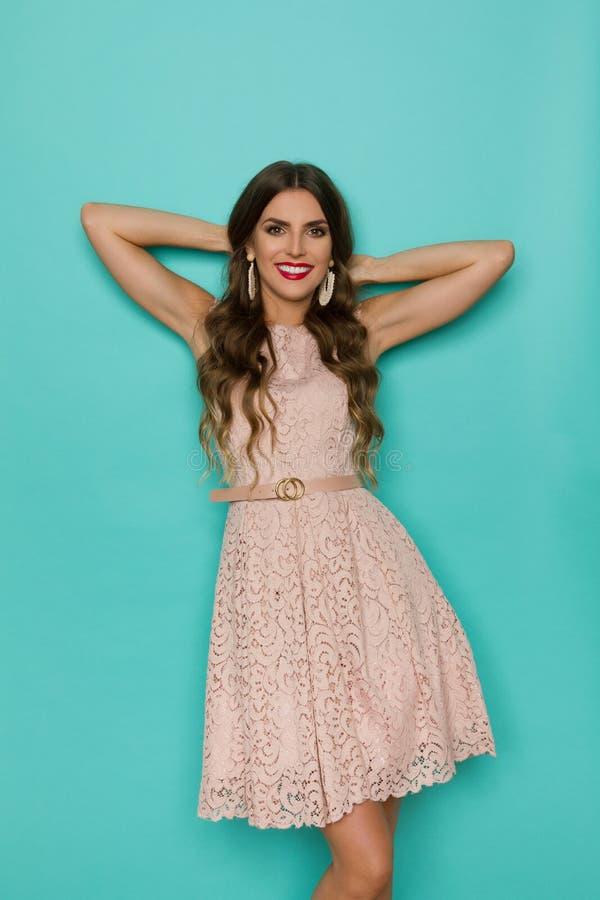 Den kopplade av unga kvinnan i beiga snör åt klänningen lutar på turkosväggen royaltyfria foton