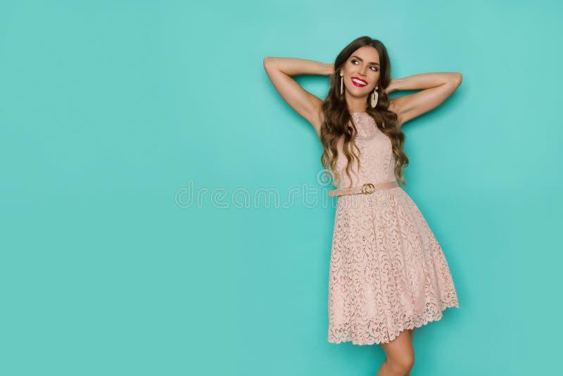 Den kopplade av unga kvinnan i beiga snör åt klänningen ser bort royaltyfria foton