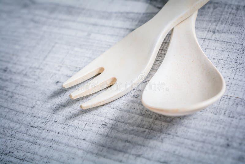 Den korsade uppsättningen av den bambugaffeln och skeden i barnformat, lär att använda bestick som ett barnbegrepp arkivbilder