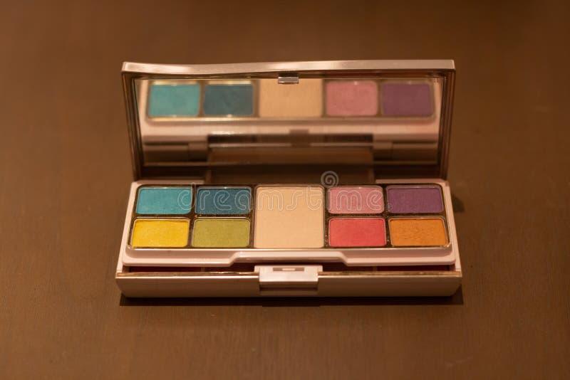 Den kosmetiska pulverasken ställde in många färg på trätabellen arkivfoton