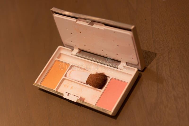 Den kosmetiska pulverasken st?llde in m?nga f?rg p? tr?tabellen arkivfoton