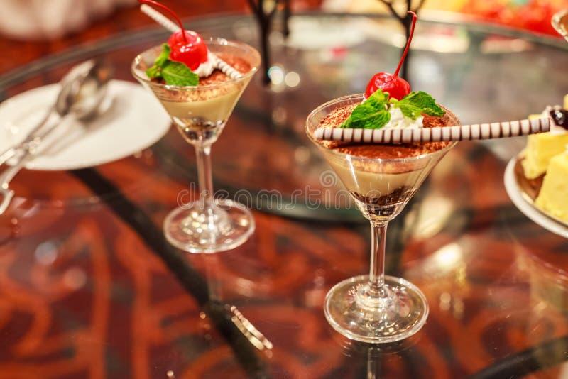 Den krämiga selektiva fokusen av choklad förspiller tiden i härliga coctailexponeringsglas med ny röd mogen körsbärsröd spiral st royaltyfria bilder