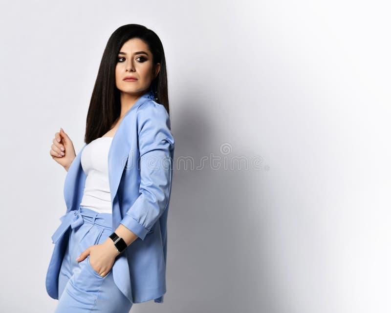 Den kraftiga affärskvinnan i blå officiell dräkt vände tillbaka och såg över hennes skuldra på utrymme för fri text på vit royaltyfria bilder