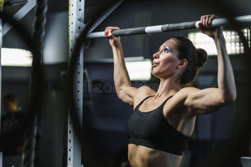 Den kraftiga attraktiva kvinnan CrossFit som instruktören drar, ups under genomkörare royaltyfria foton