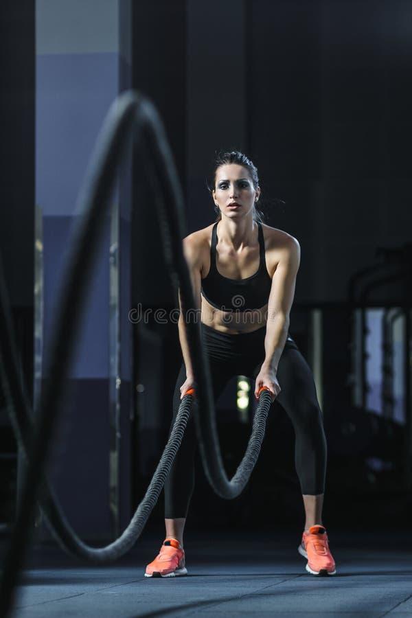 Den kraftiga attraktiva muskulösa CrossFit instruktören slåss genomkörare med rep arkivbild