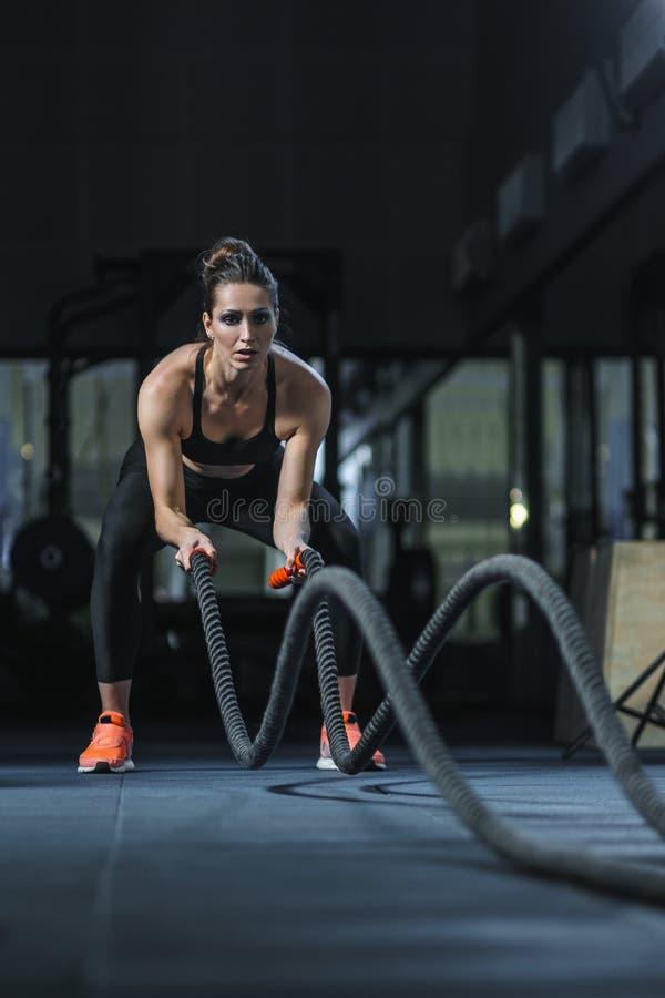 Den kraftiga attraktiva muskulösa CrossFit instruktören slåss genomkörare med rep royaltyfri fotografi