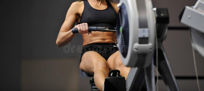 Den kraftiga attraktiva muskulösa kvinnaCrossFit instruktören gör genomkörare på inomhus roddare på idrottshallen royaltyfri foto