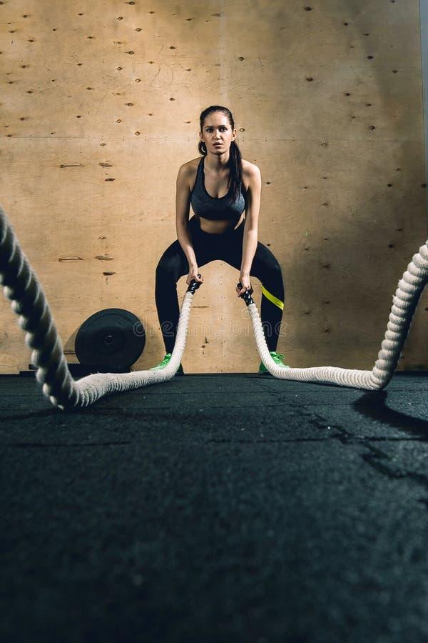 Den kraftiga attraktiva muskulösa kvinnaCrossFit instruktören slåss genomkörare med rep royaltyfri fotografi