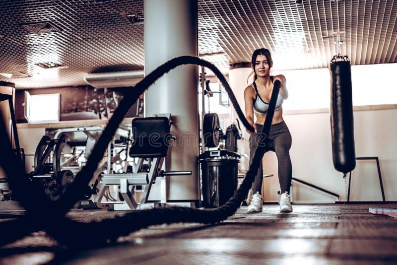 Den kraftiga attraktiva muskulösa kvinnainstruktören gör stridgenomkörare med rep på idrottshallen royaltyfri fotografi