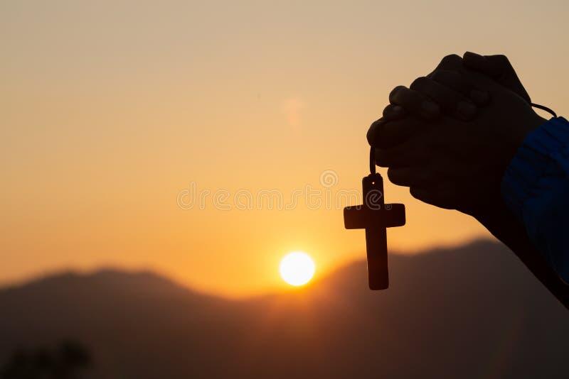Den kristna kvinnan som ber på det heliga korset i morgonen, tonåringkvinnahand med korset som ber, händer vek i bön i kyrka royaltyfria foton