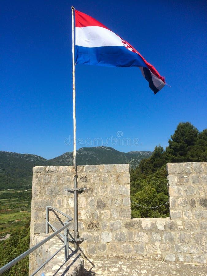 Den kroatiska flaggan på ett gammalt torn royaltyfria foton