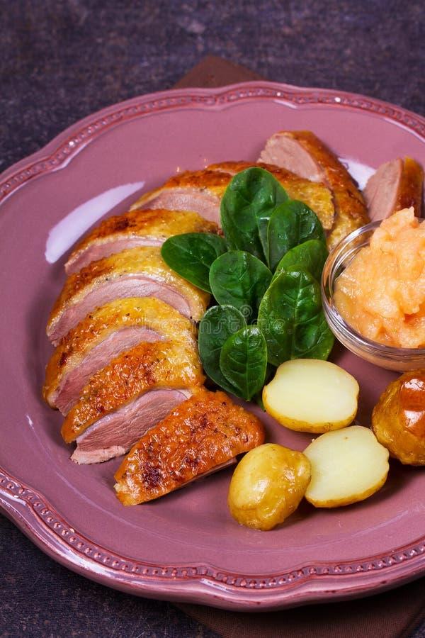 Den kryddade långsamma stekanden, äpplesås, spenat och potatis, tjänade som på rosa färgplattan royaltyfri fotografi