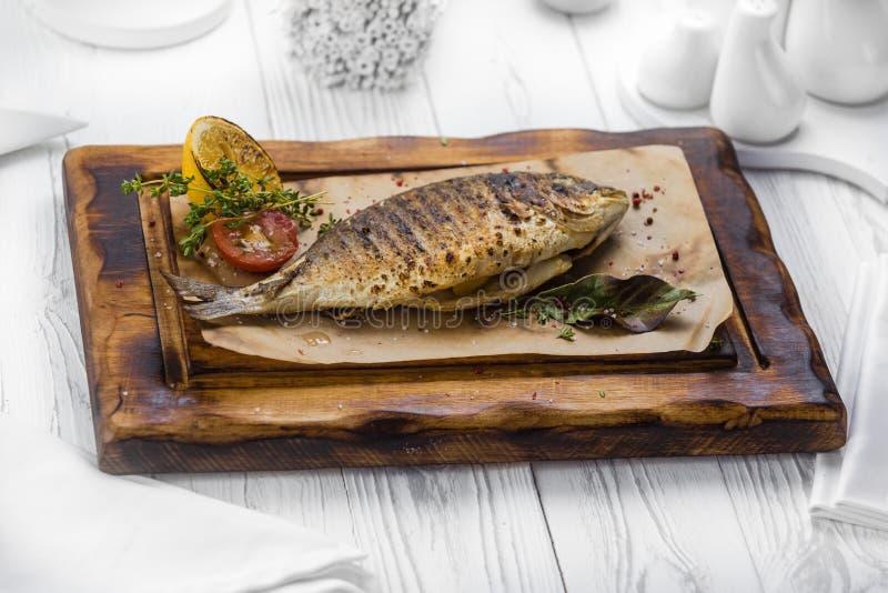 Den kryddiga grillade fisken kryddade med peppar på ett bräde arkivbilder