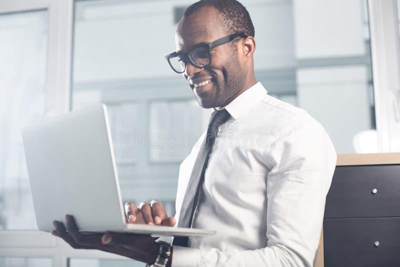 Den kvalificerade stilfulla mannen arbetar på anteckningsboken med leende arkivfoton