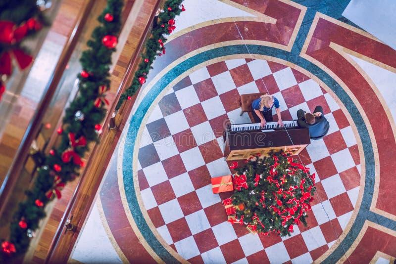 Den kvinnalekpianot och mannen sitter Julkonsert på gallerian Loppfoto 2014 december arkivfoton