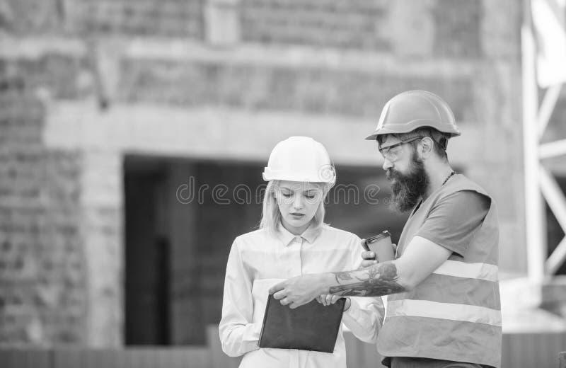 Den kvinnateknikern och byggm?staren meddelar konstruktionsplatsen Begrepp f?r konstruktionslagkommunikation F?rh?llanden mellan royaltyfri fotografi