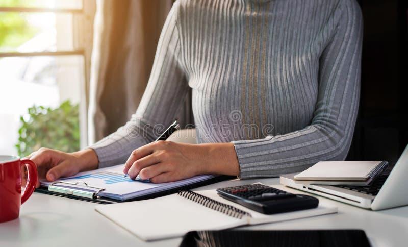 Den kvinnliga affärsmannen beräknar financials med grafpapper på bärbar datordatoren royaltyfri bild