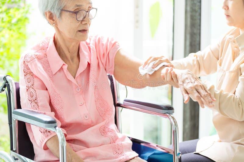 Den kvinnliga anhörigvårdaren eller sondottern som hjälper den höga kvinnan för, gnider kroppen som är torr till lättnadsfeber el arkivbild