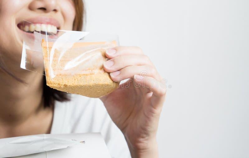 Den kvinnliga asiatet äter karamellkakan royaltyfri bild
