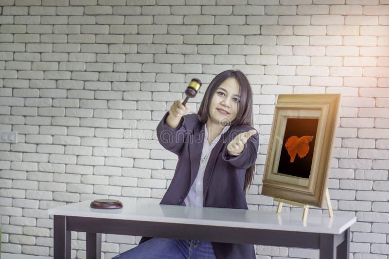 Den kvinnliga auktionsförrättaren ler, och punktfingrar till auktionvinnarestridigheten fiskar, med en vit bakgrund arkivbild