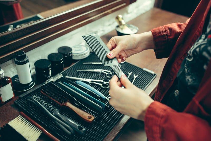 Den kvinnliga barberaren i barberare shoppar royaltyfri fotografi