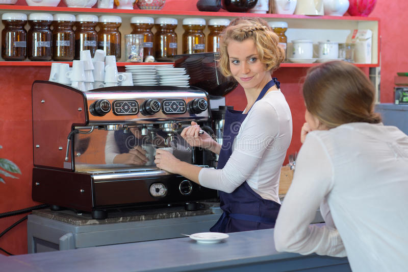 Den kvinnliga bartendern gör kaffe på stången royaltyfri fotografi
