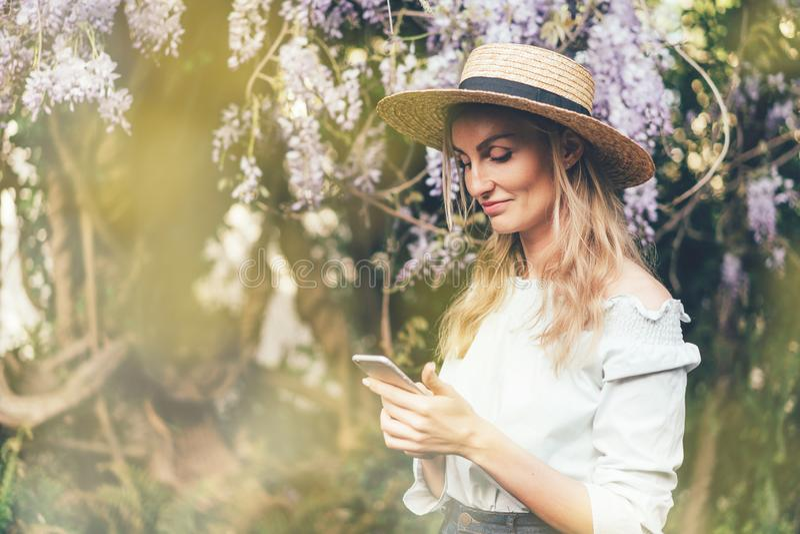 Den kvinnliga bloggeren ser in i telefonen royaltyfria foton