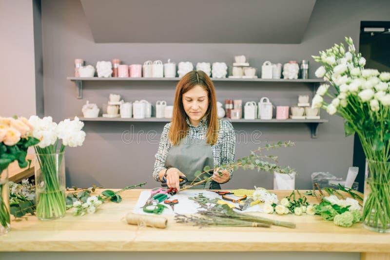 Den kvinnliga blomsterhandlaren förbereder blommasammansättning arkivbilder