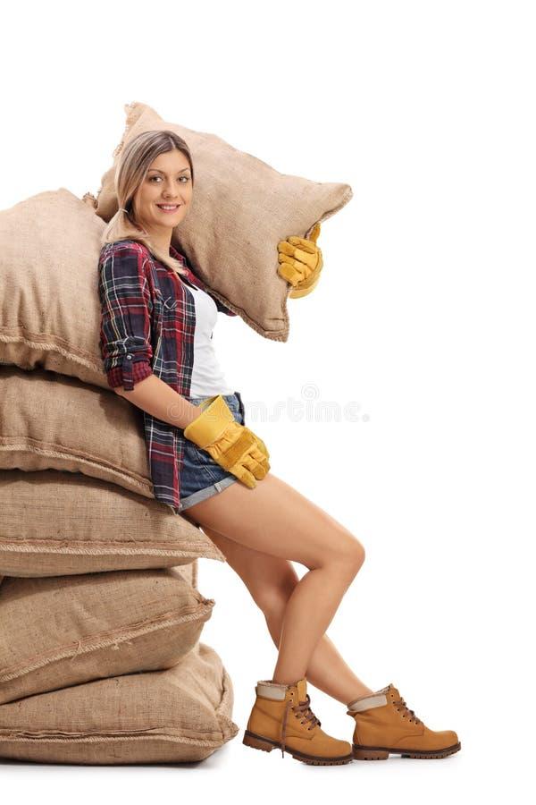 Den kvinnliga bondebenägenheten på en hög av säckväv plundrar royaltyfri foto
