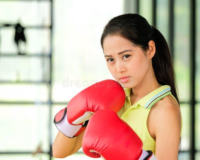 Den kvinnliga boxaren bär röda tumvanten och övar i idrottshall royaltyfri fotografi