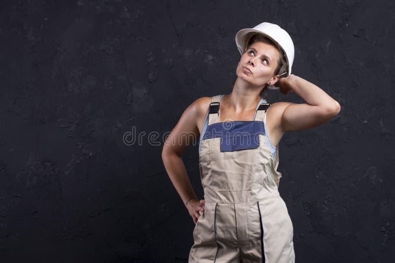 Den kvinnliga byggmästaren poserar för kamera i studio Stående av den härliga byggmästaren för kvinnaarbetare i likformig med den fotografering för bildbyråer