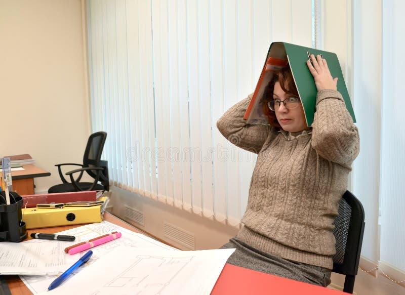 Den kvinnliga chefen med fasa ser och rymmer mappen med dokument på huvudet arkivbilder