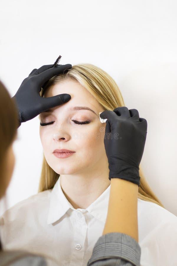 Den kvinnliga cosmetologisten utf?r ?gonbrynkorrigering p? h?rliga modeller i sk?nhetmottagningsrummet Flickans framsida ?r en bl arkivfoton