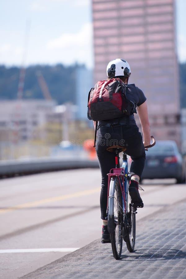 Den kvinnliga cyklisten med ryggsäcken cyklar längs cykelbanan along fotografering för bildbyråer